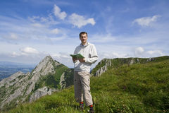 Mountain tourist with map over blue sky Royalty Free Stock Photo