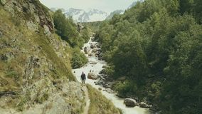 Mountain tourist walking along rapid river back view. Hiking mountain stock footage