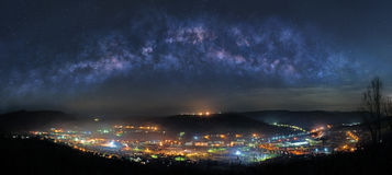 Mountain town at night. Panoramic picture of mountain town at night with majestic Milky Way on the sky Royalty Free Stock Photo