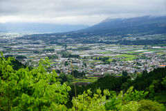 Mountain and town panorama view with green bush foreground Royalty Free Stock Photo