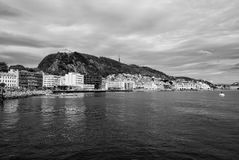 Mountain and town view from sea water in Alesund, Norway. Alesund, Norway - January 16, 2010: mountain and town view from sea water on cloudy sky background Royalty Free Stock Image