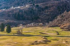 Mountain city and sunny spring meadow in the Italian Alps, Trentino, Italy royalty free stock images