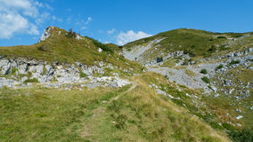 Mountain trail. Narrow mountain trail in the foreground. Hills and blue sky in the back Royalty Free Stock Image
