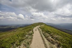 Mountain trail in Bieszczady National Park. Mountains scenery on cloudy day. Grass and meadow Poloniny in The Bieszczady National Park in Poland. Hiking trail Stock Photography