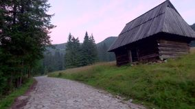 Mountain trail between cottages in valley Chocholowska at sunrise, Poland. Europe stock video footage
