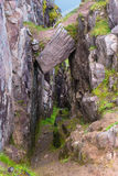 Mountain trail descending into canyon with hanging rock above en Stock Images