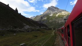 Mountain Train in Swiss Alps During Summer. A mountain train crosses the Swiss Alps in Switzerland during the summer Royalty Free Stock Image