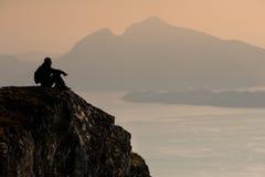 Mountain traveler. A man sitting on edge of a mountain Stock Photography