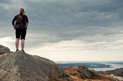 Mountain traveler. A girl looking at a valley from top of a mountain Royalty Free Stock Images