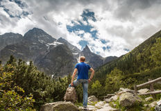 Mountain traveler looks on wild rocks Royalty Free Stock Photography