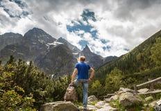Mountain traveler looks on wild rocks Royalty Free Stock Photography