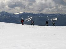 Mountain Trekkers. Four trekkers are hiking with snowshoes high up on the slopes of Mt. Rainier. They are outlined against other peaks in the Cascade mountains Stock Images
