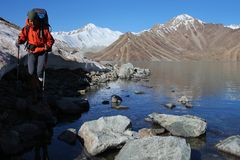 Mountain trekking. Young woman with backpack on the shore of high altitude mountain lake Royalty Free Stock Images