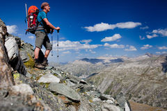 Mountain trekking. Young man with backpack on a mountain hike Royalty Free Stock Photography