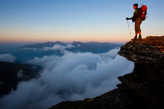 Mountain trekking. Man with backpack high above the misty mountain valley Stock Images