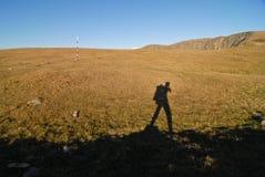Mountain trekking. The shadow of a tourist on a mountain trail Stock Photos