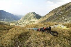 Mountain Trekking Poles in the Grass on Mountain Peak Stock Photography