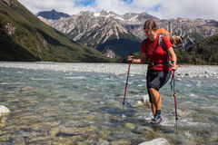 Mountain trekking. Young woman fording cold mountain stream Royalty Free Stock Images