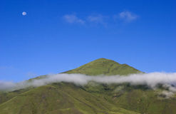 Mountain  under  blue sky. Mountain with fog  under  blue sky  ,the moon can be seen ,taken in early morning Royalty Free Stock Photography