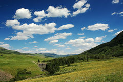 Mountain Valley. Landscape view of lush green mountain valley under a beautifully clouded blue sky royalty free stock photo