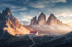 Mountain valley with beautiful house and church at sunset. In autumn. Landscape with buildings, high rocks, trail, blue sky and sunlight. Mountains in Tre Cime stock photos