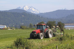Mountain Valley Farm and Tractor. A farm in the mountains with a red tractor in the foreground Royalty Free Stock Photos