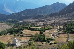 Mountain valley: fields on terraces descending from the slopes, green trees, white Buddhist stupa to the fore, high rock, Tibet. Royalty Free Stock Images