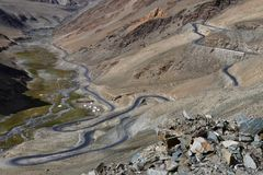 Mountain valley: gray asphalt strip winds along the slope of the hill and descends into valley to the blue river, pass in the moun. Mountain valley: gray asphalt Stock Image