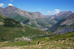 Mountain valley landscape. Countryside authentic alpine mountain landscape with green slopes, pastures, small isolated village in valley and two hikers. alpes Stock Photography
