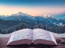 Mountain valley in a light of sunrise on the pages of book Stock Photos