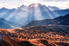 Mountain valley lighted with bright sunbeams at sunset. In autumn in Dolomites, Italy. Landscape with mountains, rolling hills with orange trees and grass royalty free stock images