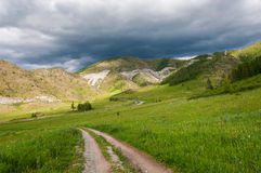 Mountain valley meadow road clouds Royalty Free Stock Images