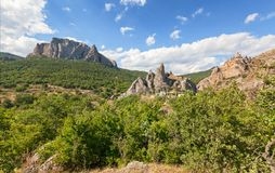 Mountain valley with Parsuk-Kaya mountain towering over the forest and Delikli-Kaya rock against the sky with clouds. Mountains of the Crimean Peninsula Royalty Free Stock Images