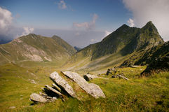 Mountain valley on summer day in wilderness. Mountain valley with rocks and green grass on summer day in wilderness romanian carpathians Stock Images