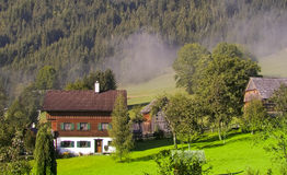 Mountain valley village in austria. Alps mountain valley gosau village in austria houses on green summer meadow early morning fog Royalty Free Stock Images