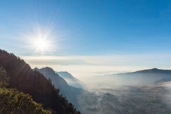 Mountain valley was covered by morning mist after sunrise with the sun and clear blue sky Stock Images