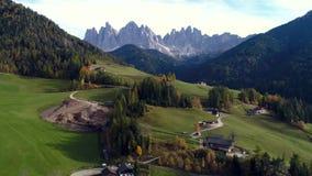 Mountain View aéreo da vila alpina, de prados verdes e de pastos, picos Cumes de Dolomiti de Tirol sul filme