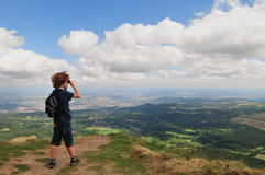 Mountain view child. Picture of a young boy (7) standing on the edge of a mountain side looking over the beautiful valley below with binoculars. Puy de Dome Stock Images