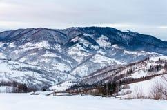 Mountain View del invierno en la cerca de madera del amanecer en la nieve, azul, t verde Foto de archivo