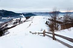 Mountain View del invierno en la cerca de madera del amanecer en la nieve, azul, t verde Imagen de archivo