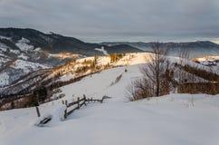 Mountain View del invierno en la cerca de madera del amanecer en la nieve, azul, t verde Imagen de archivo libre de regalías