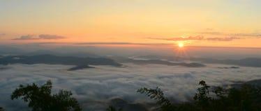 Mountain View del panorama en el sol que sube con la niebla en el campo Fotos de archivo