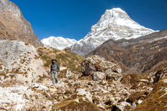 Mountain View of high snow capped Peak and Backpacker walking Stock Photos