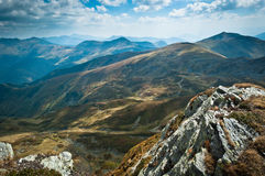 Mountain view. A landscape from Rodnei Mountains, Romania, featuring some big rocks in the foreground (crystalline schists) and some high peaks in the distance Royalty Free Stock Images