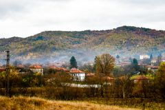 Foggy village. Mountain view of little village houses in a foggy autumn day stock photo