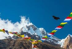 Mountain View maestoso con le bandiere e l'uccello buddisti di preghiera Immagini Stock