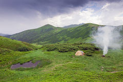 Mountain view with a tent, camping fire and a little lake in fro Royalty Free Stock Images