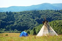 Mountain view with tent and teepee Stock Images