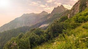 Mountain View in una foschia leggera al tramonto attraverso l'erba e gli arbusti immagini stock