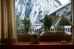 Mountain view from the window in house in Alpes, Italy Lamp and decorative old vintage kettle Stock Photography